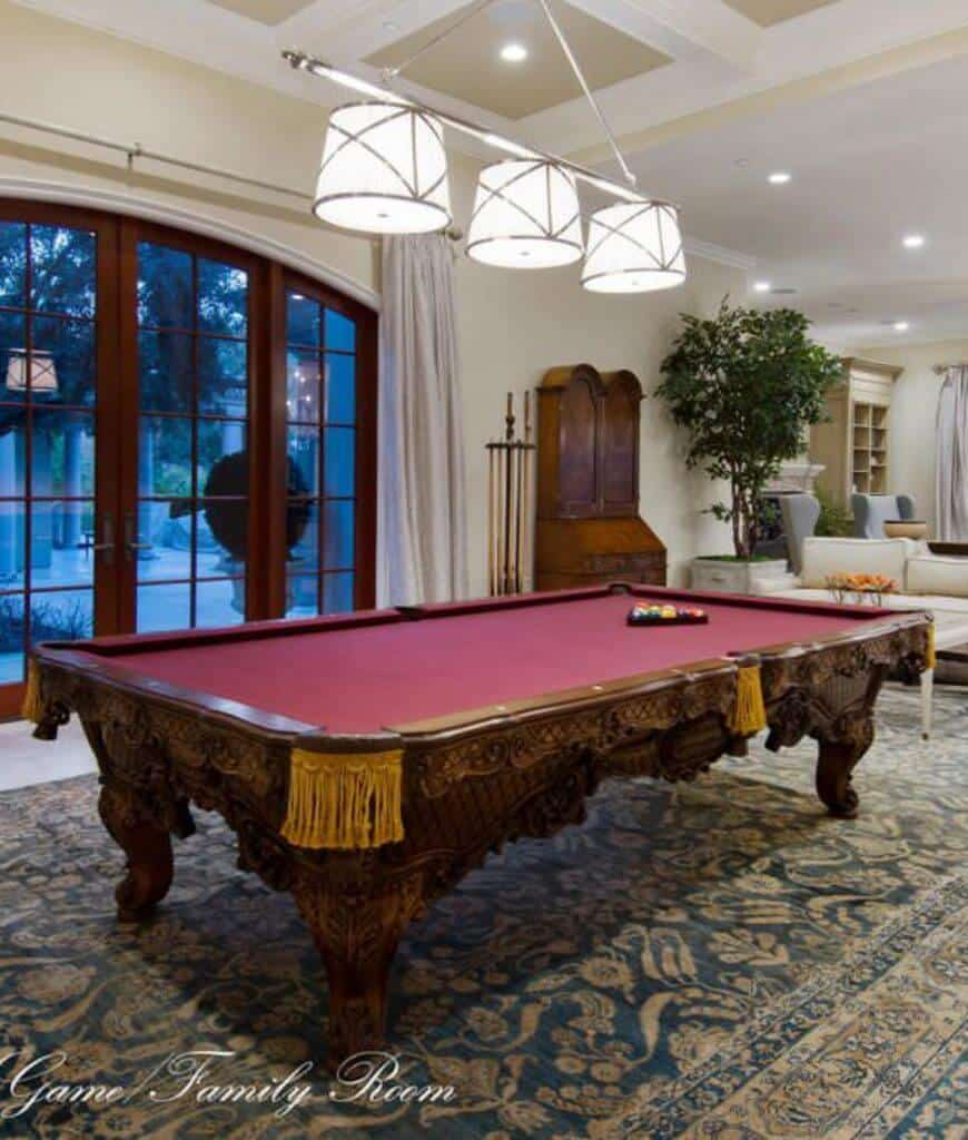 Traditional family room showcases a carved wood pool table that sits on a classic area rug lighted by drum pendants that hung from the coffered ceiling.