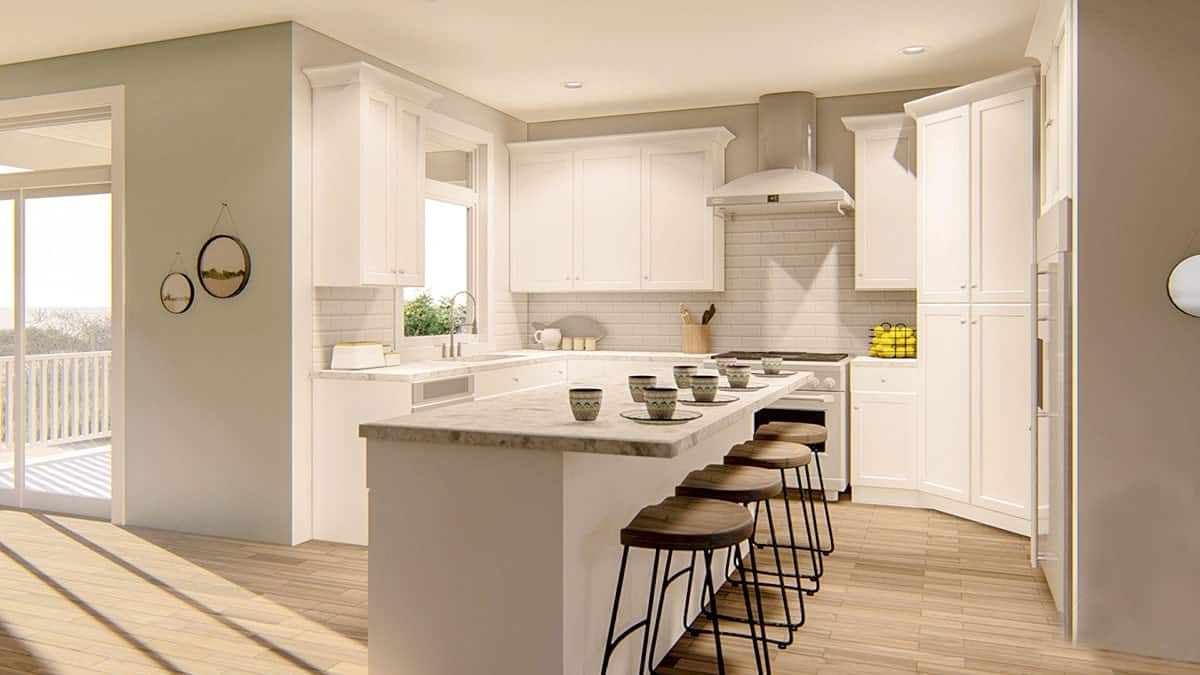 The kitchen is equipped with white cabinetry, white appliances, and a marble top breakfast island lined with wooden bar stools to match the hardwood flooring.