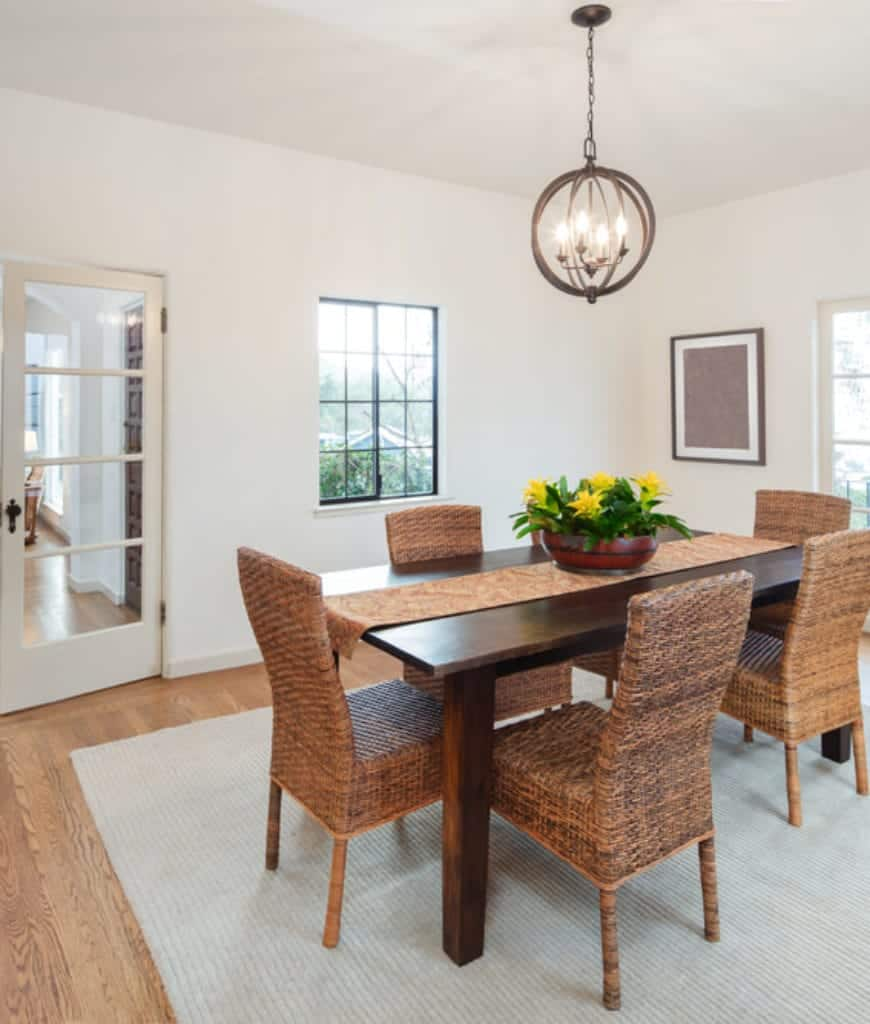Bright dining room with a spherical chandelier and wooden dining table lined with a lovely runner that complements with the wicker chairs on a gray rug.