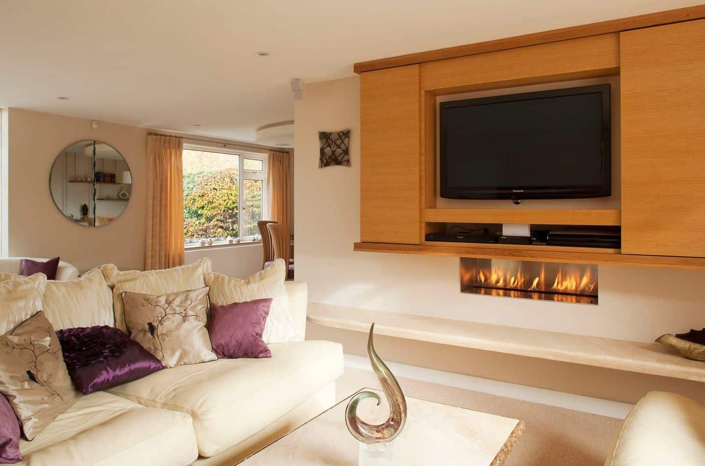 Fabulous living room showcases a television fitted in the middle of wooden storage that hung above the modern fireplace. It includes a marble coffee table and white sectional accented with purple pillows.