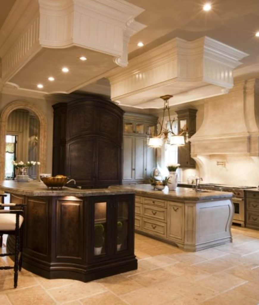Gourmet kitchen offers full height storage cabinets and double island bars illuminated by drum chandelier and recessed lights fixed on the white drop ceiling.