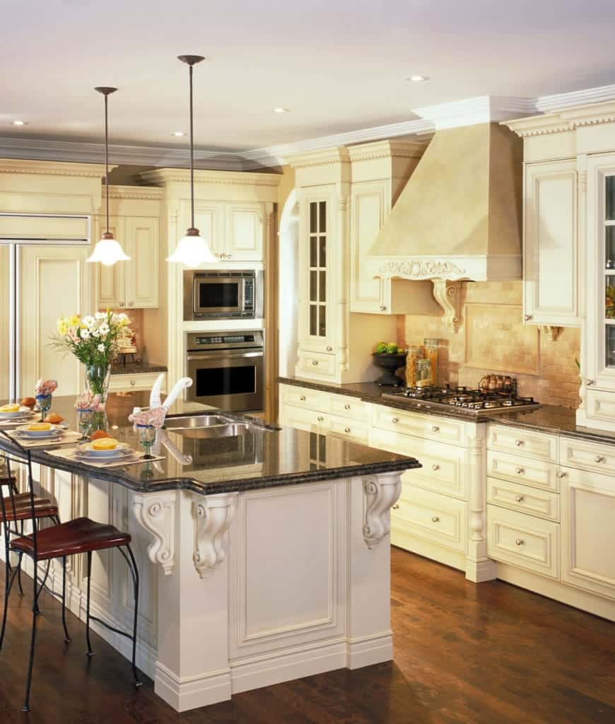 This kitchen offers pendant lights that hung over the granite top breakfast bar and cream cabinetry with stainless steel appliances inset.