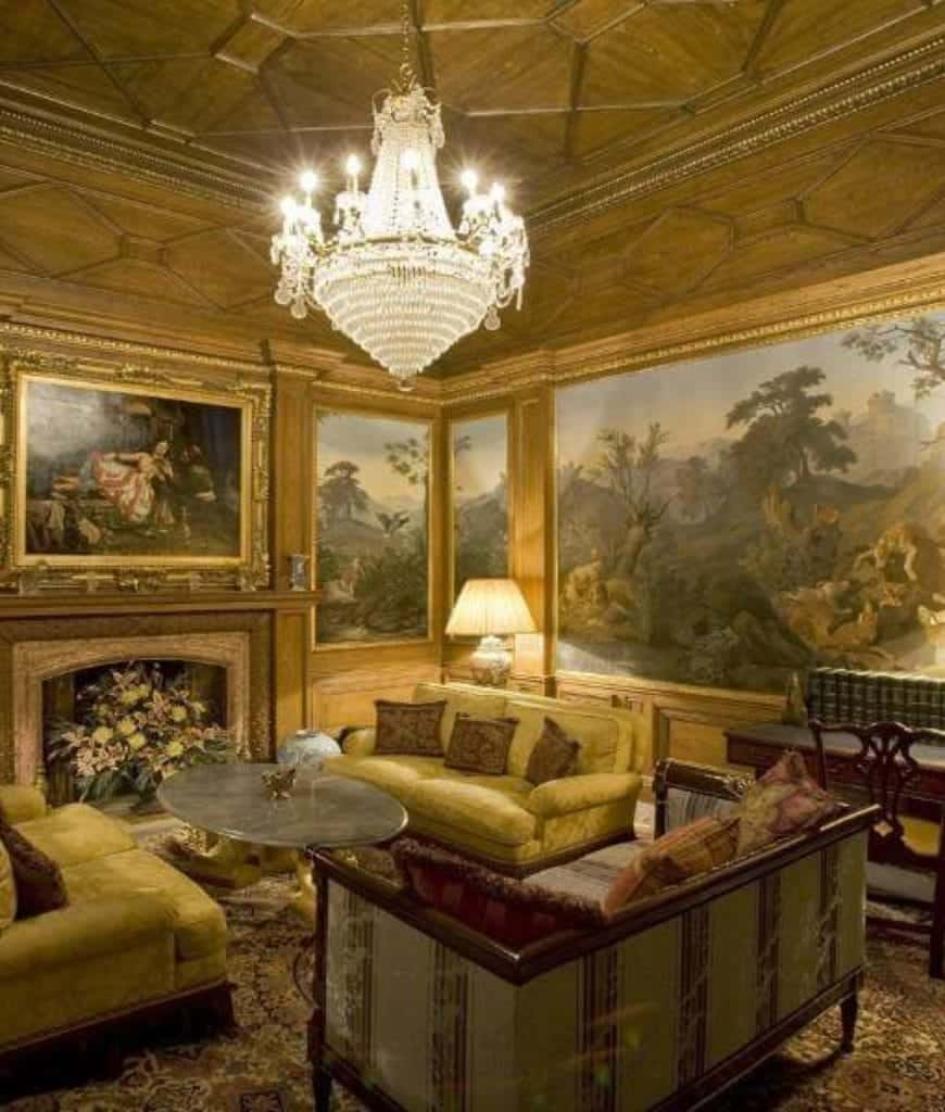 Deluxe living room decorated with magnificent paintings along with a fancy chandelier that hung from the gold ornate ceiling. It has striped and yellow green sofas that sit in front of the fireplace covered with lovely flowers.