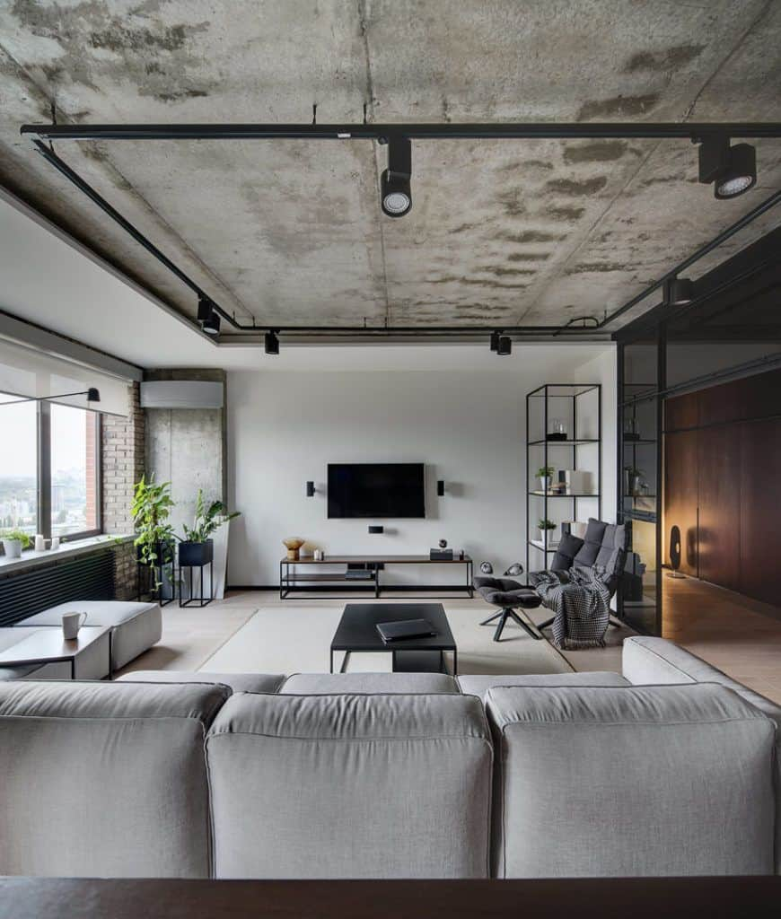 Industrial living room illuminated by track lights fixed to the distressed white ceiling along with natural light that flows through the glass windows covered with translucent roller blind.