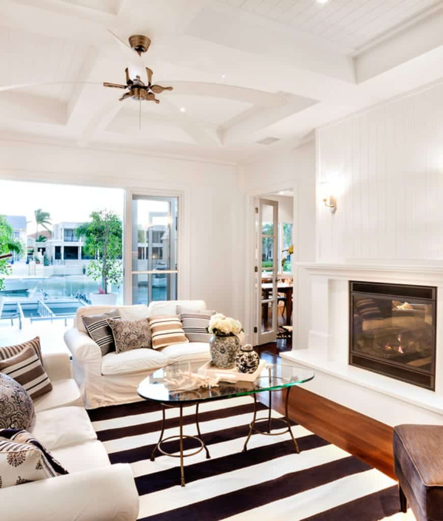 Airy living room accented with a striped rug and pillows that lay on white sofas accompanied by a glass top coffee table and fireplace fixed to the white beadboard wall.