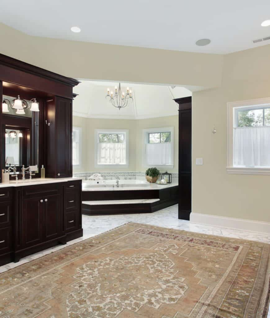 Primary bathroom boasts a chandelier and marble flooring topped with a vintage rug. It has a soaking bathtub and dark wood sink vanity with mirror.