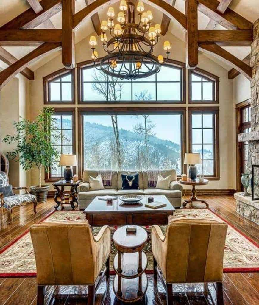 Craftsman living room features rich wood plank flooring topped by a red area rug along with a wrought iron chandelier that hung from the cathedral ceiling framed with wood beams.