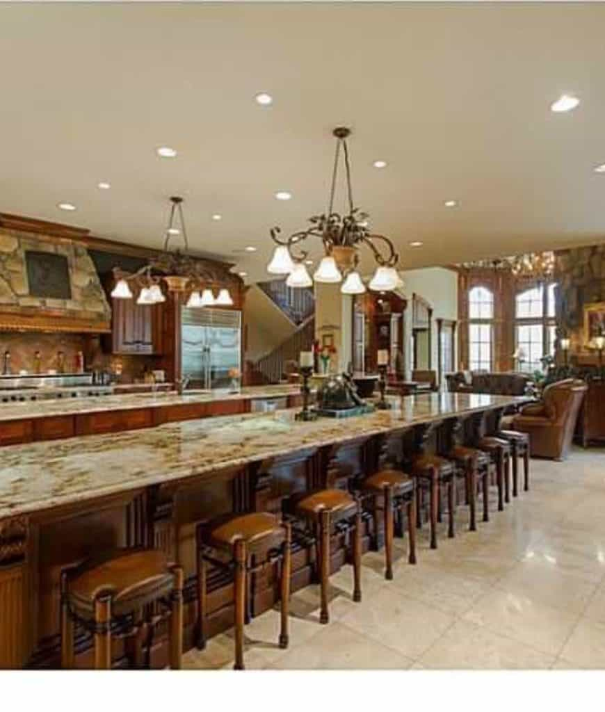 This kitchen features a stone range hood and lengthy island bar lined with brown leather stools and illuminated by classic chandeliers.
