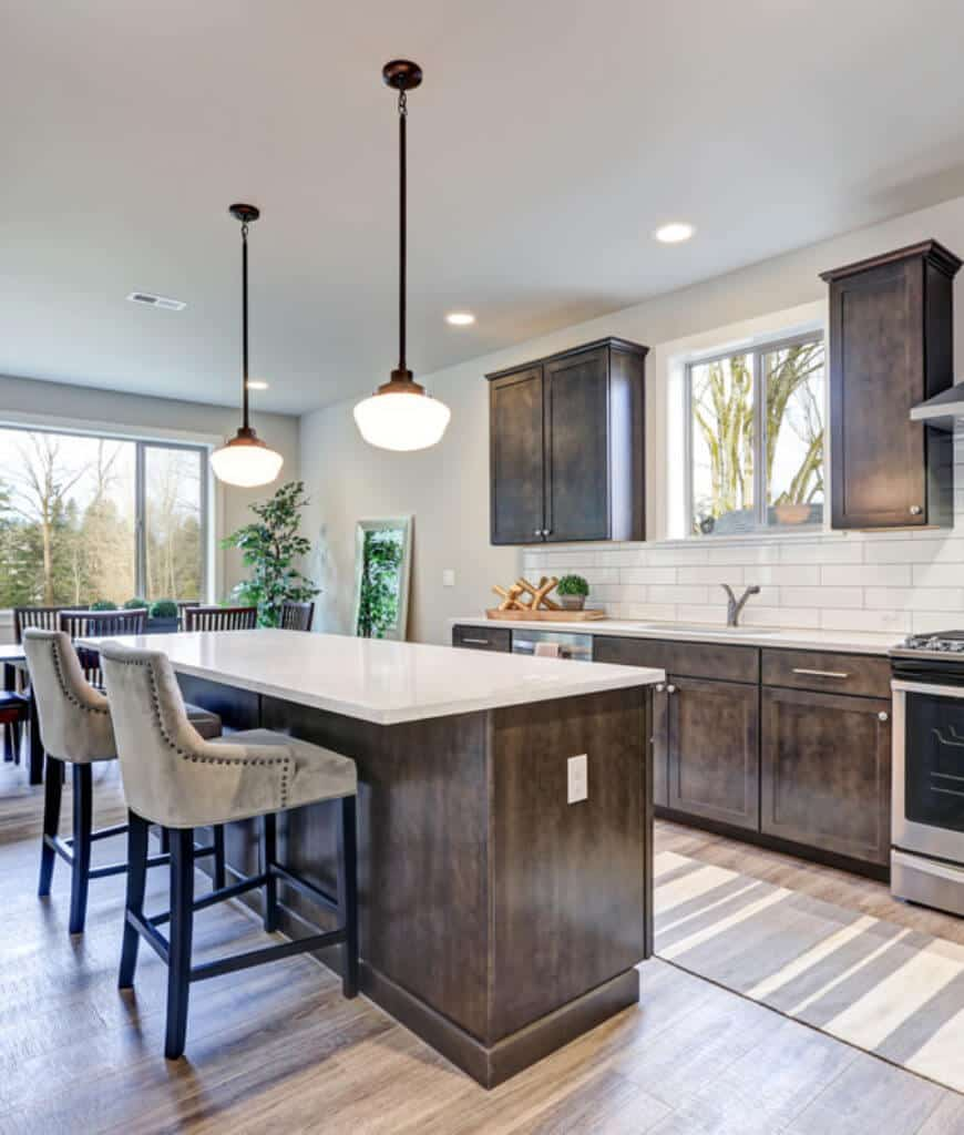 Fresh kitchen with glass slider and natural hardwood flooring topped by a striped runner. It includes pendant lights and a wooden island bar paired with beige upholstered counter chairs.