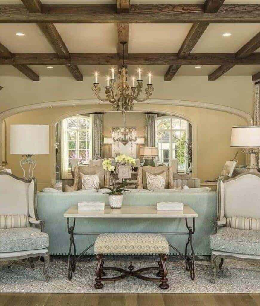 Classy living room with metal console table and multiple seats lighted by table lamps and a candle chandelier that hung from the wood beam ceiling.