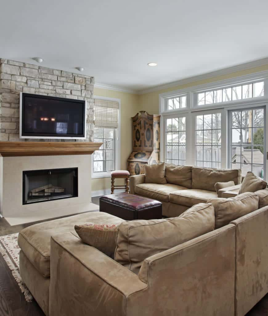 Yellow living room furnished with brown velvet sectionals and a leather ottoman that faces the fireplace fixed on the stone brick pillar.