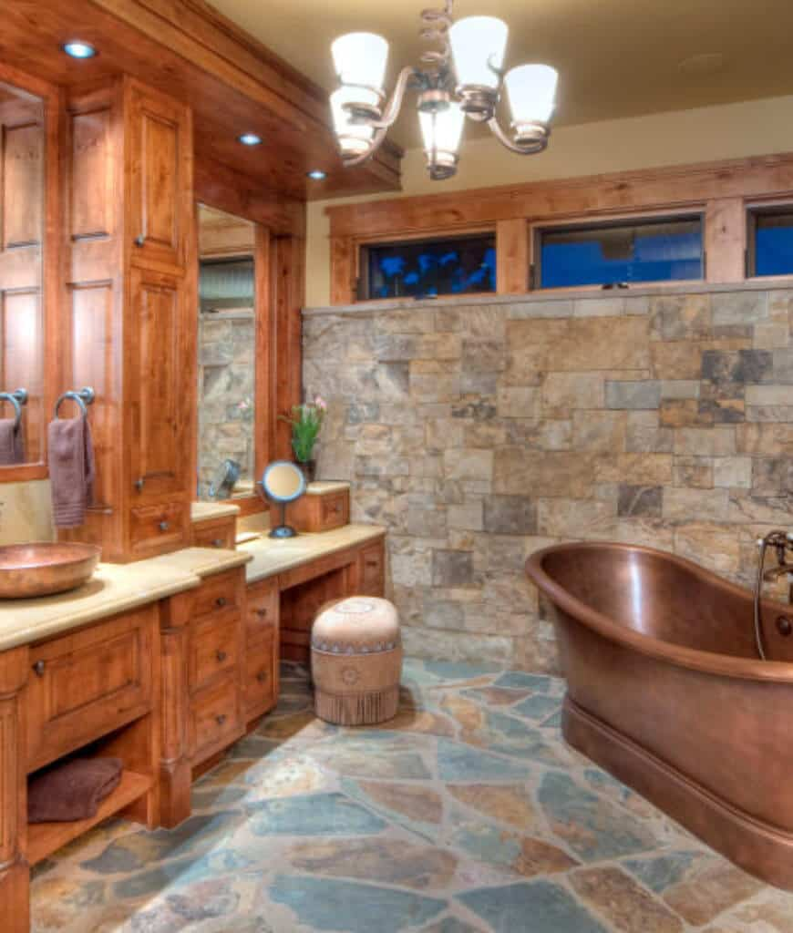 Rustic primary bathroom showcases a vessel sink vanity with wooden drawers and a copper bathtub that sits on flagstone flooring.