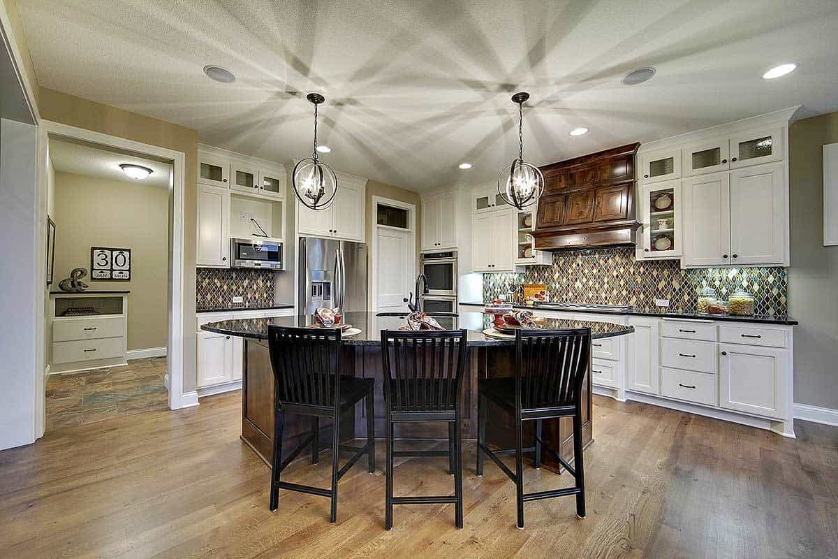 The dark wood and dark granite of the kitchen island matches well with the dark stools and hardwood flooring. These are then contrasted by the bright white shaker cabinets and drawers of the cabinetry.