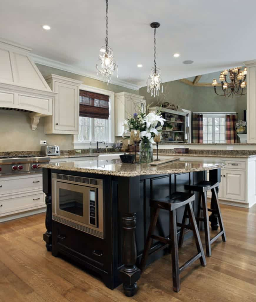 Crystal chandeliers illuminate this kitchen featuring white cabinetry contrasted with a black kitchen island topped with granite counter and paired with matching black bar stools.