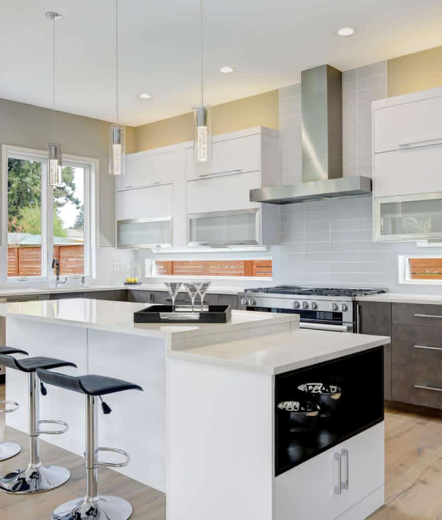 Black barstools sit at a white raised breakfast island in this kitchen with modern pendant lights and a sleek vent hood fixed on the gray tile backsplash.