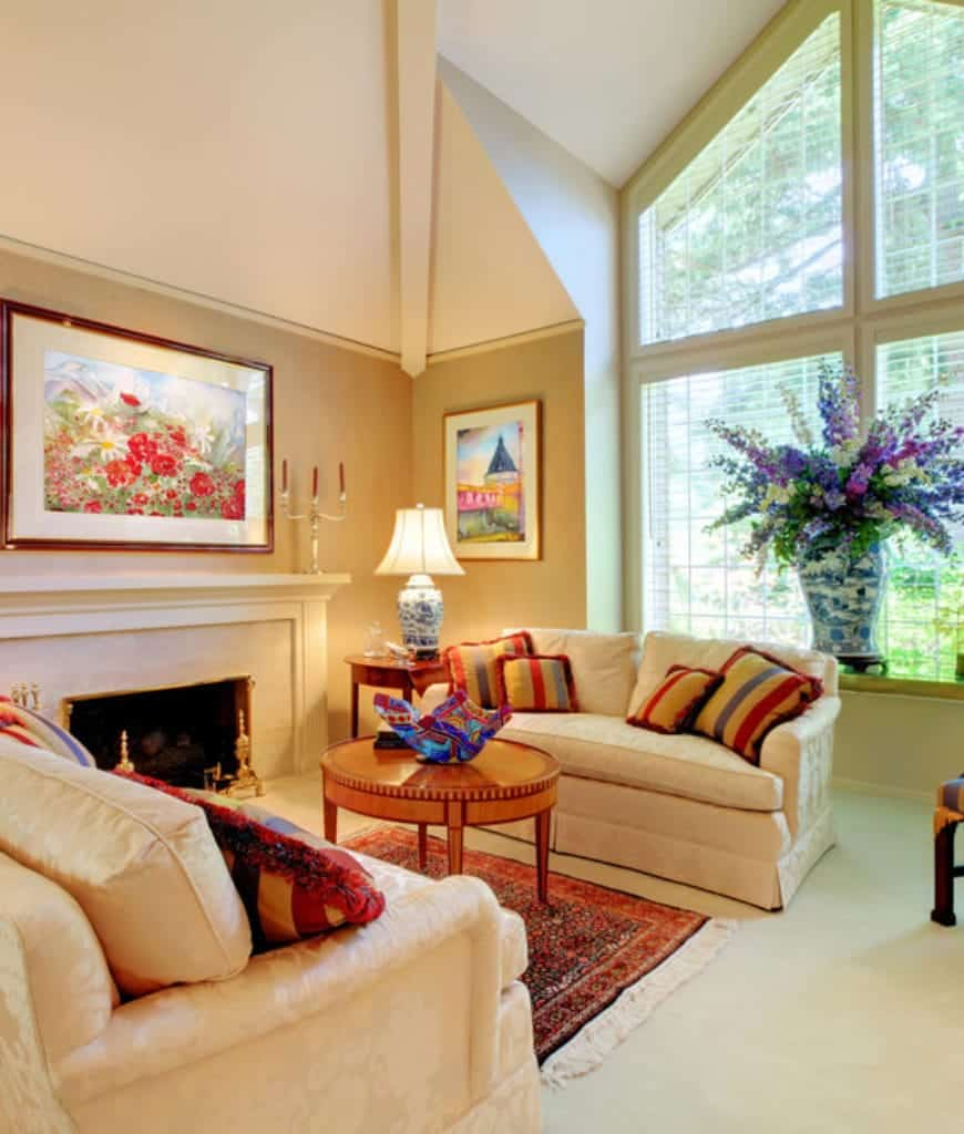 Bright living room designed with gorgeous flowers and colorful wall arts mounted on the beige wall. It has a round coffee table and cream sofas accented with bold striped pillows.