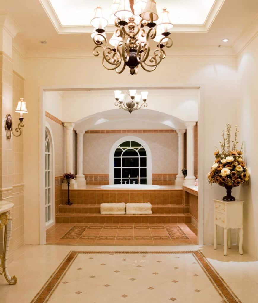 Elegant primary bathroom boasts a bathtub framed with white columns and illuminated by an ornate chandelier that hung from the tray ceiling.