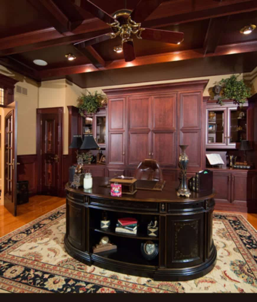 An oval-shaped desk sits on the vintage rug in this home office with rich hardwood flooring and coffered ceiling mounted with ceiling fan and recessed lighting.