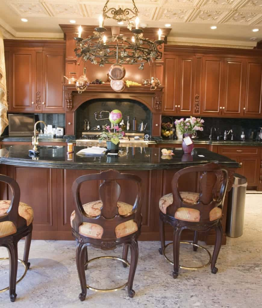 This kitchen showcases stylish round back chairs and a brown breakfast bar illuminated by a gorgeous round chandelier that hung from the white ornate ceiling.