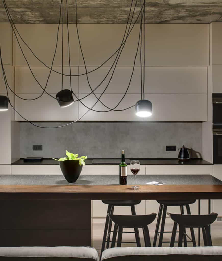 Sleek kitchen with white cabinetry and an island bar illuminated by spider industrial pendants that hung from the rustic ceiling.