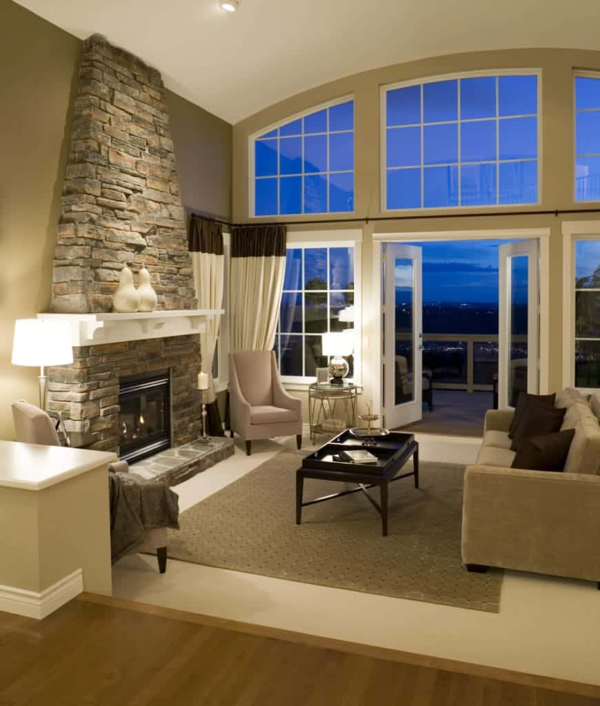 Modern living room with glass windows and doors that open to the veranda framed with glass railing. It includes a stone fireplace lined with white mantel.