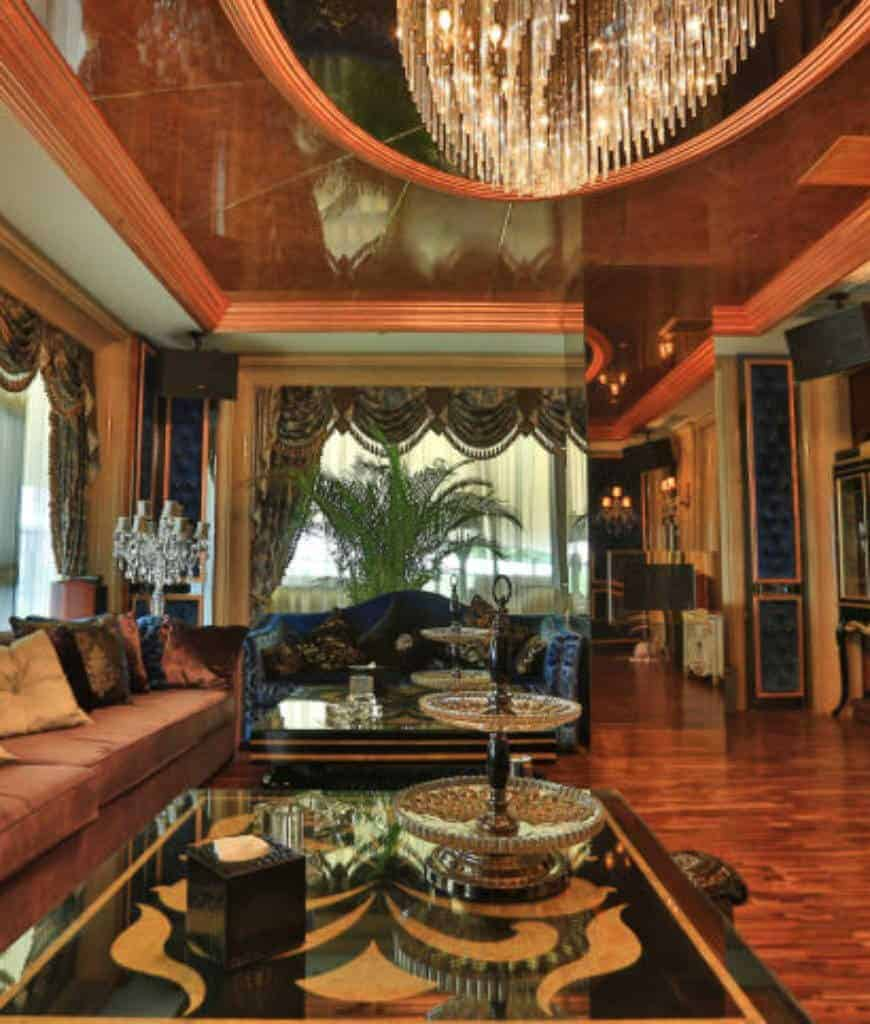 Luxury living room with rich hardwood flooring and full height windows dressed in white sheer curtains and elegant valences. It includes a marble ceiling with a hanging glam chandelier.