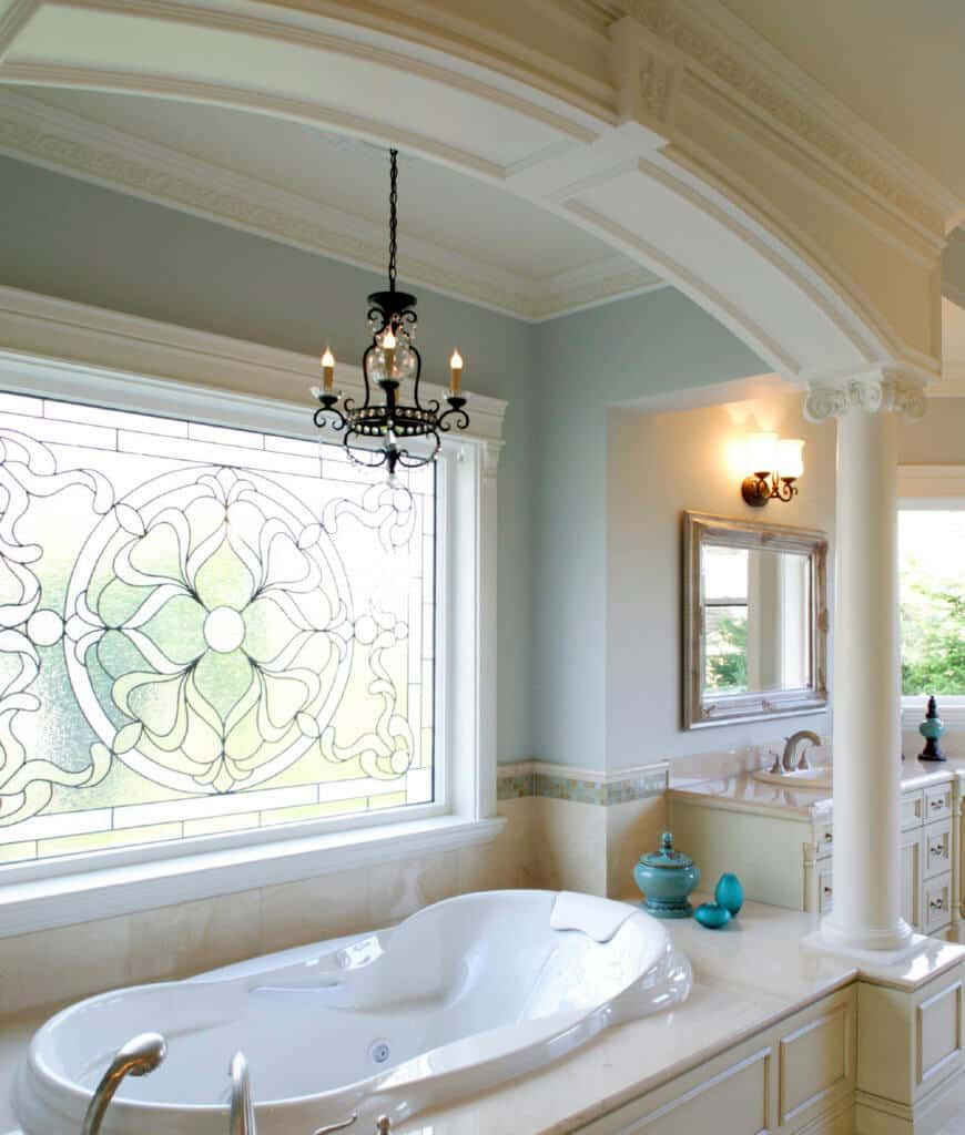 A vintage candle chandelier illuminates this primary bathroom with a drop in bathtub beneath the lovely stained glass windows.