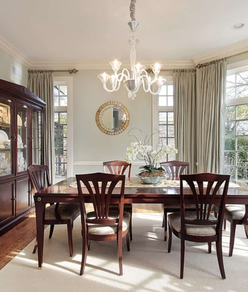 Fabulous dining room decorated with a stylish round mirror and glass chandelier that hung over the wooden dining set on a beige rug.