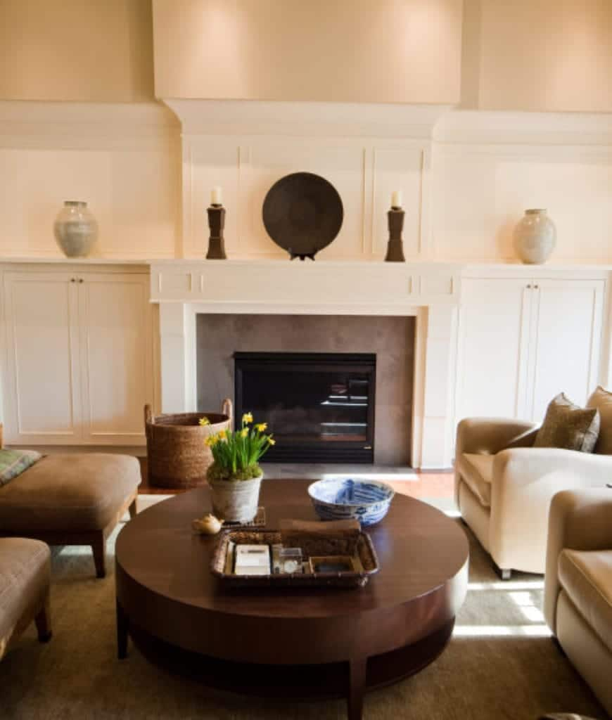 A rattan basket sits in front of the fireplace topped with candles and a decorative black plate in this living room with comfy seats and a huge round coffee table.