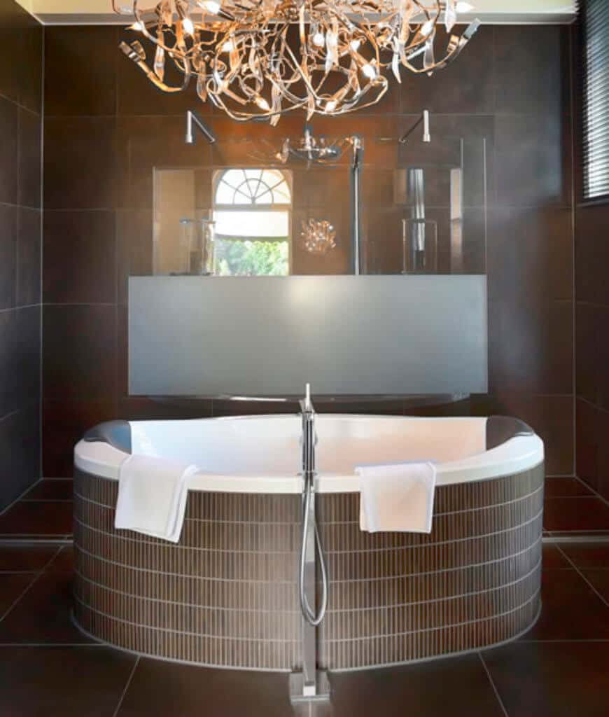 Stylish primary bathroom with a walk-in shower and statement chandelier that hung over the soaking tub clad in brown tiles.