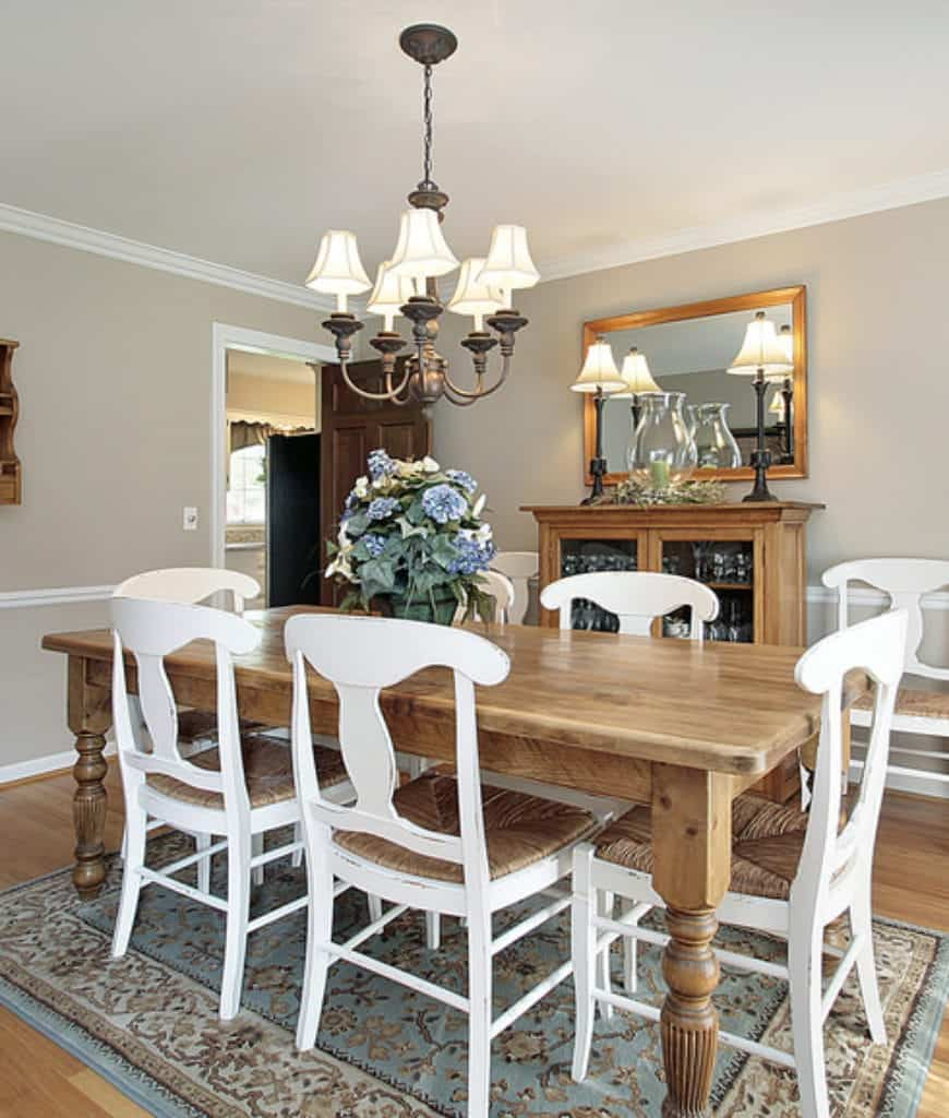 White dining chairs sit at a natural wood table in this dining room with chandelier and charming blue rug.