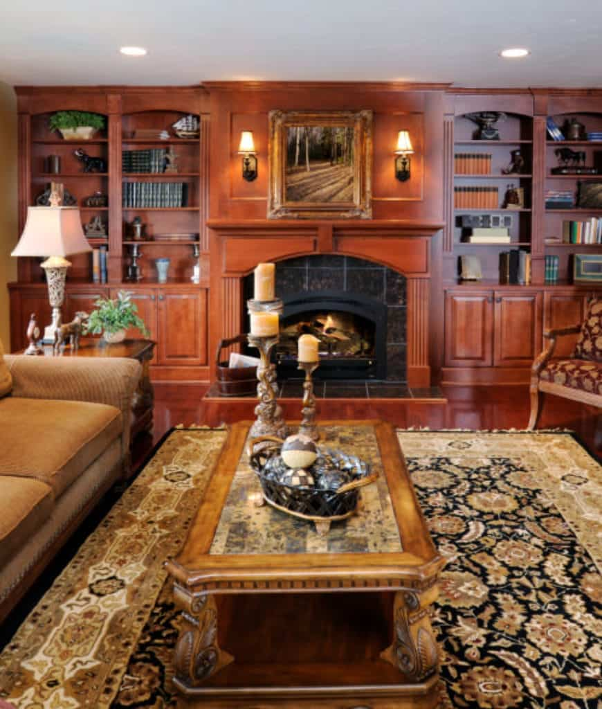 Formal living room showcases built-in shelving and a fireplace with black marble surround tiles. It is topped with a classy framed wall art that's lighted by sconces.