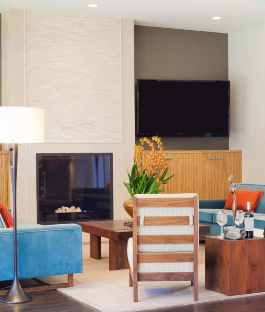 Gorgeous living room accented with blue sofas and vibrant orange pillows illuminated by a white drum floor lamp.