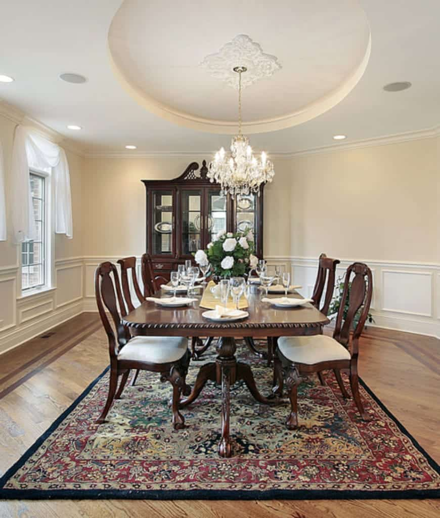 White dining room showcases a dark wood display cabinet complementing with the dining set lighted by a fancy chandelier that hung from the round tray ceiling.