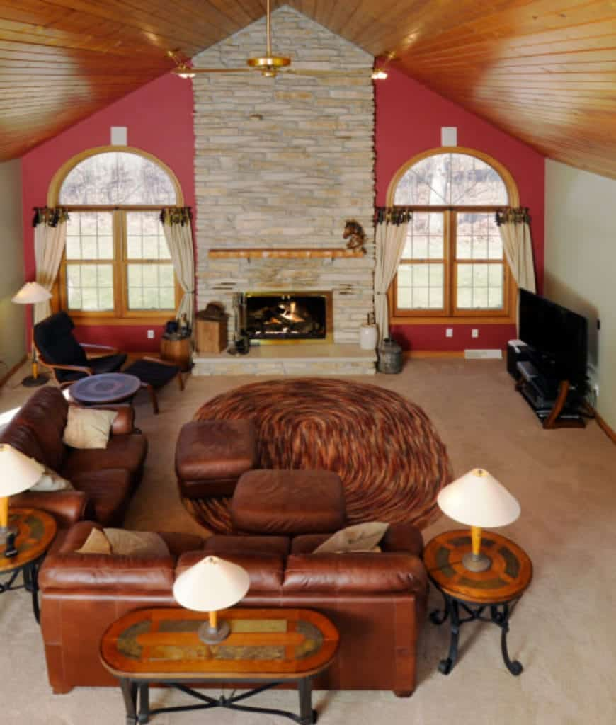 Eclectic living room with wooden cathedral ceiling and arched windows dressed in white draperies. It has a pink accent wall lined with a stone brick pillar that's fitted with a brass fireplace.