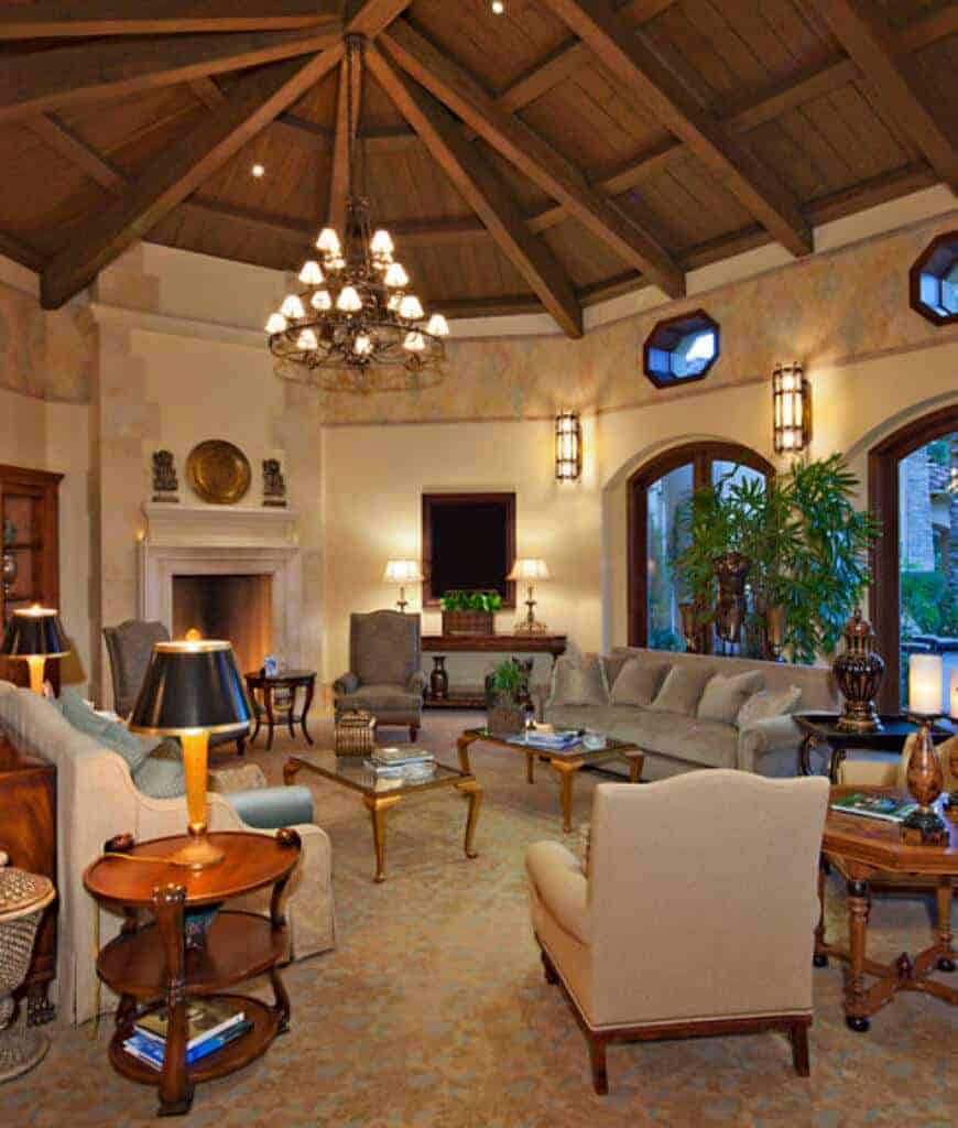 Tropical living room offers a fireplace and comfy seats along with wooden and glass top tables lighted by a vintage chandelier that hung from the dome wood beam ceiling.