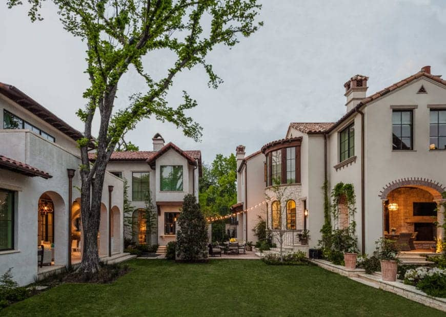 A lavish lawn filled with greenery serves as a bridge to the three separate houses in this multi-sectioned Spanish complex. It features massive glass windows and arched entryways paired with clay-tiled roofing and soaring chimneys atop of traditional Gable roofs.