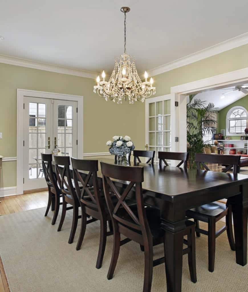 An airy dining room offers a French door that opens to the patio and dark wood dining set on a beige area rug lighted by a crystal chandelier.