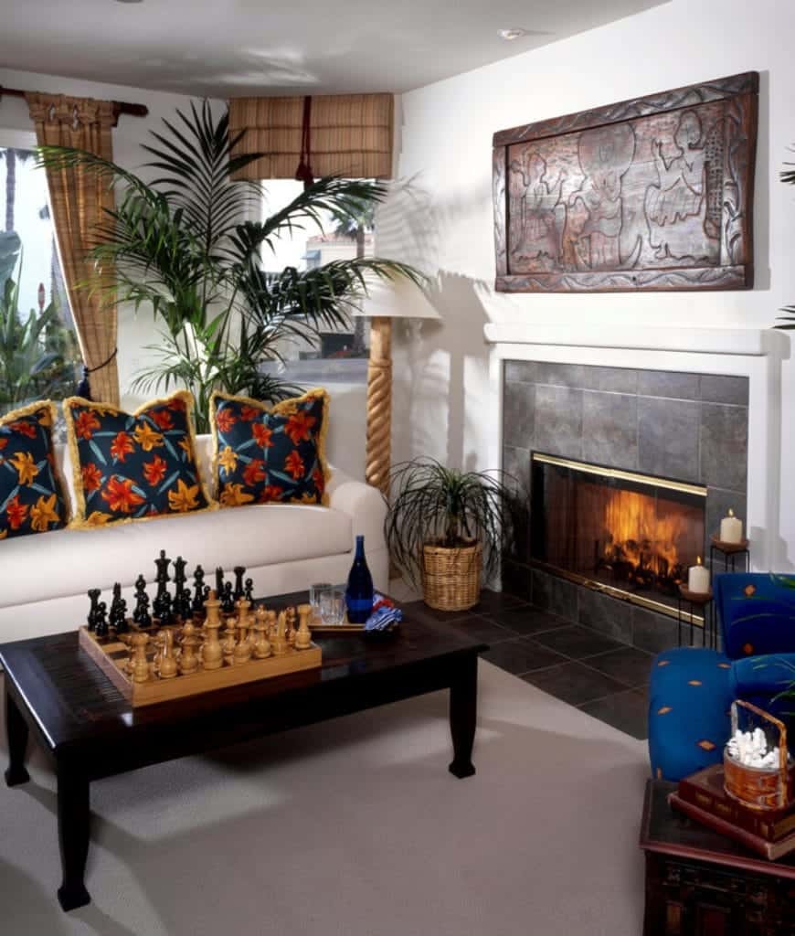 White living room features a dark wood coffee table and metal fireplace along with a white sofa accented with blue floral pillows.