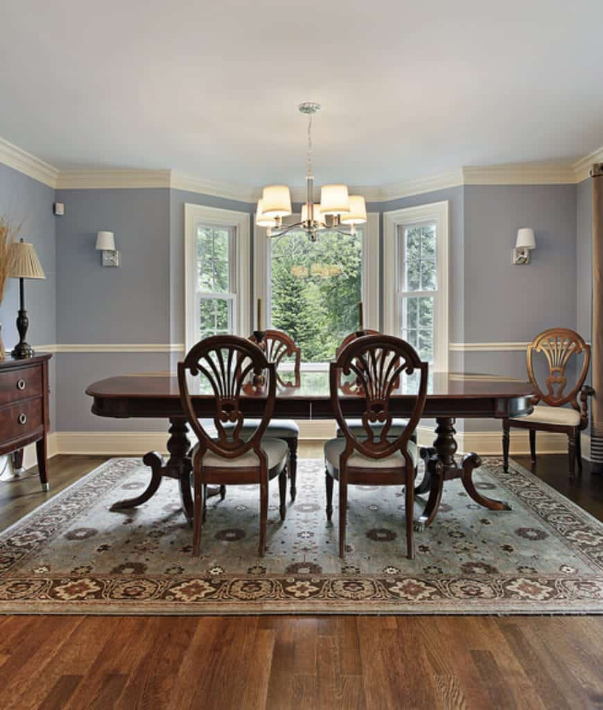 Blue dining room with an oval dining set and round back chairs that sit on a floral rug. It is illuminated by wall sconces and a chandelier that hung from the white ceiling lined with crown molding.