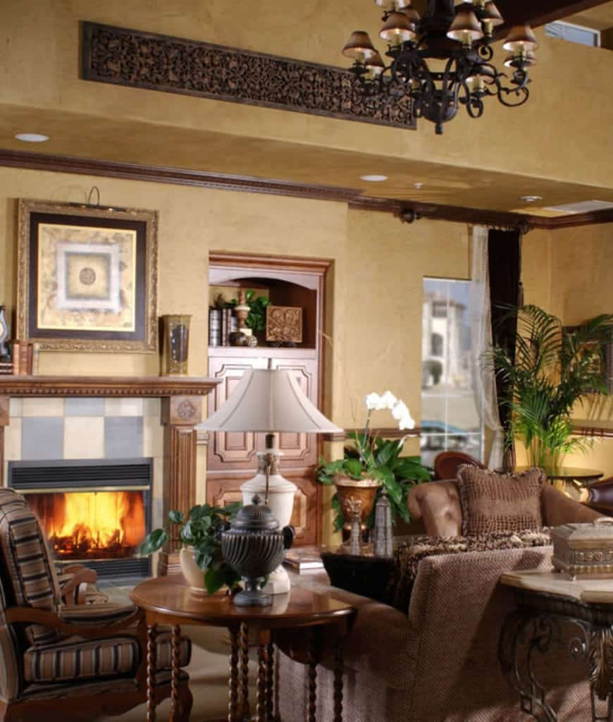 Spanish style living room illuminated by a vintage chandelier and white table lamp that sits on a round side table. It has a built-in cabinet and fireplace with checkered surround tiles and ornate wooden mantel.