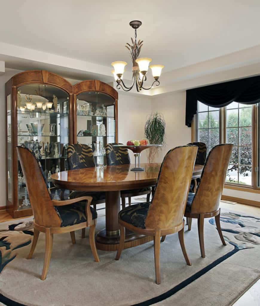 Natural light streams through the wooden framed windows dressed in black valence in this dining room with a classy dining set accompanied by arched display cabinets.