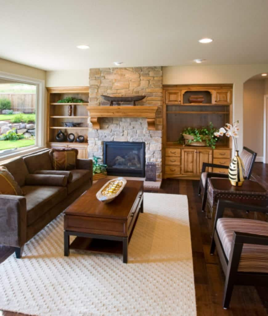 Living room with cozy seats and a stone fireplace fixed in between wooden built-in shelves. It includes a picture window and wooden coffee table that sits on a white textured rug.