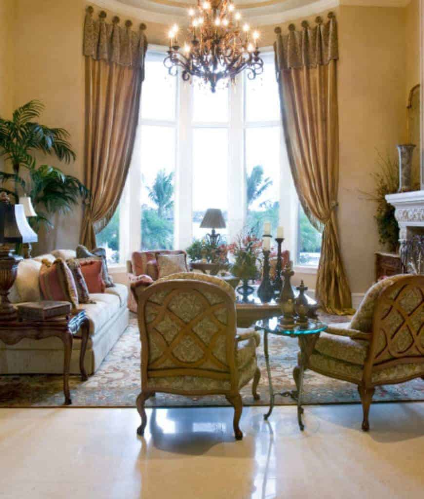 Sophisticated living room with marble flooring and floor to ceiling windows dressed in gold draperies. It includes a glam chandelier and comfy seats filled with multicolored pillows.