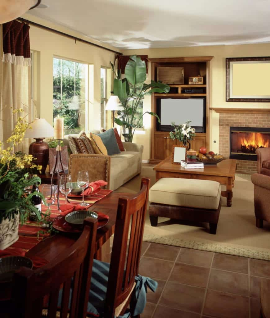An open living room with a brick fireplace and wooden coffee table paired with beige stool and sofa that's filled with multi-colored pillows.