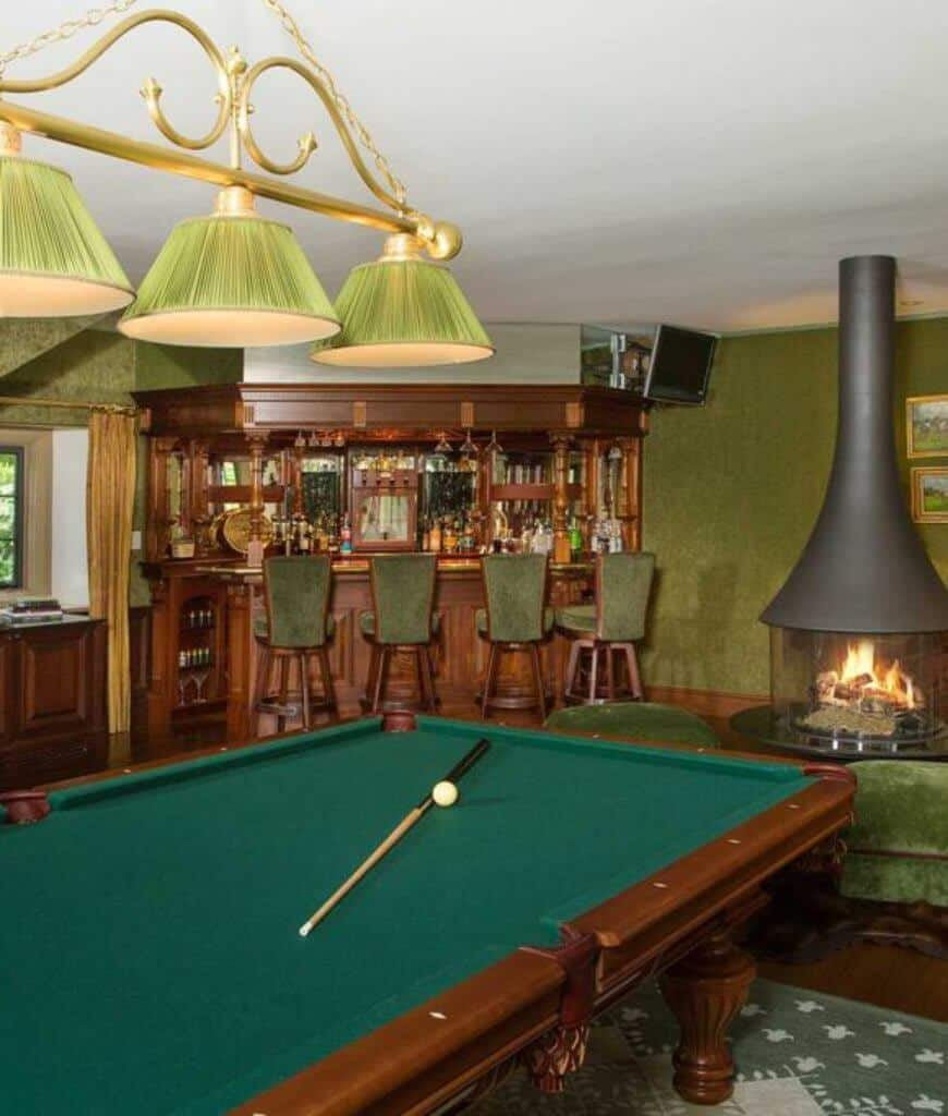 Green man cave offers a freestanding fireplace next to the corner bar area along with a pool table that sits on a patterned rug lighted by a brass pendant.