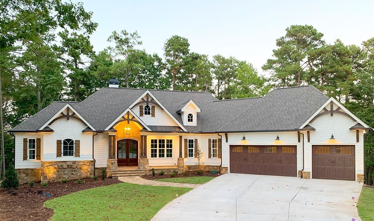This craftsman-style home features decorative trims and stone accents that complement well with the lush green lawn and concrete driveway.