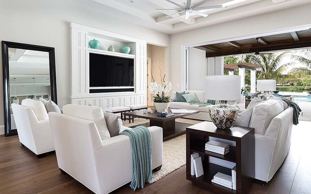 This living room has a bright and white theme to its beamed ceiling, walls and the sofa set. These are then contrasted by the dark hardwood flooring, square wood coffee table and the sofa side table.