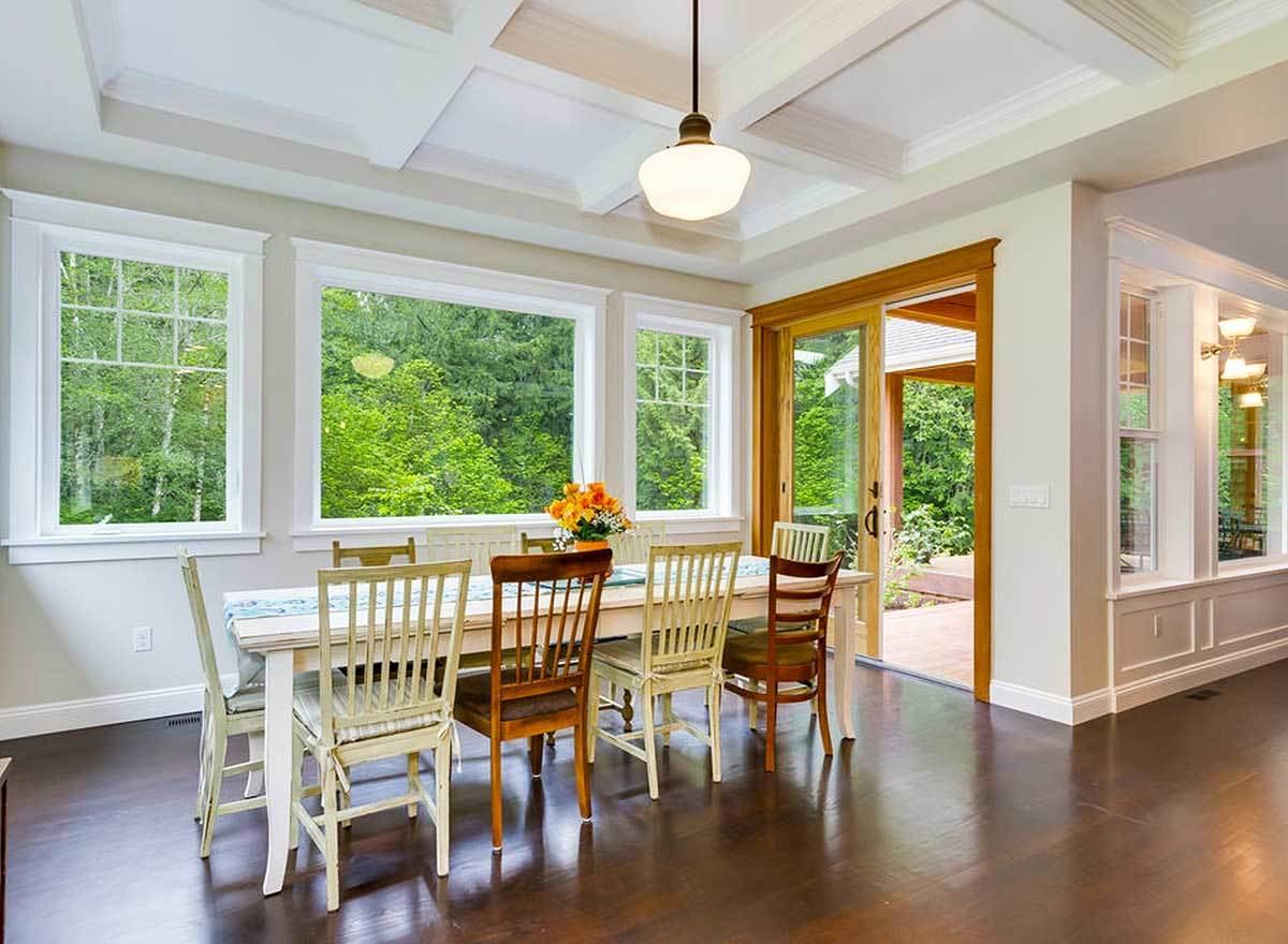 Bright dining room with a white coffered ceiling and a rectangular dining table surrounded by wooden and white cushioned chairs.
