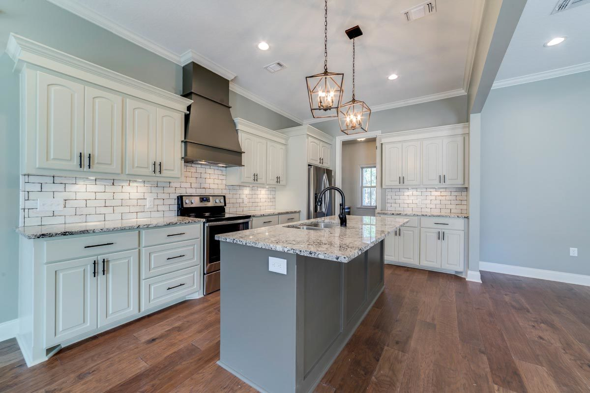The neutral walls and cabinets of this gourmet kitchen are softened by natural hardwood flooring. Subway tile backsplash and caged pendants add nice touches.